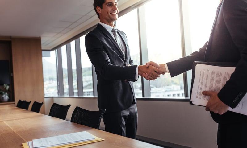 Businessmen shaking hands in boardroom