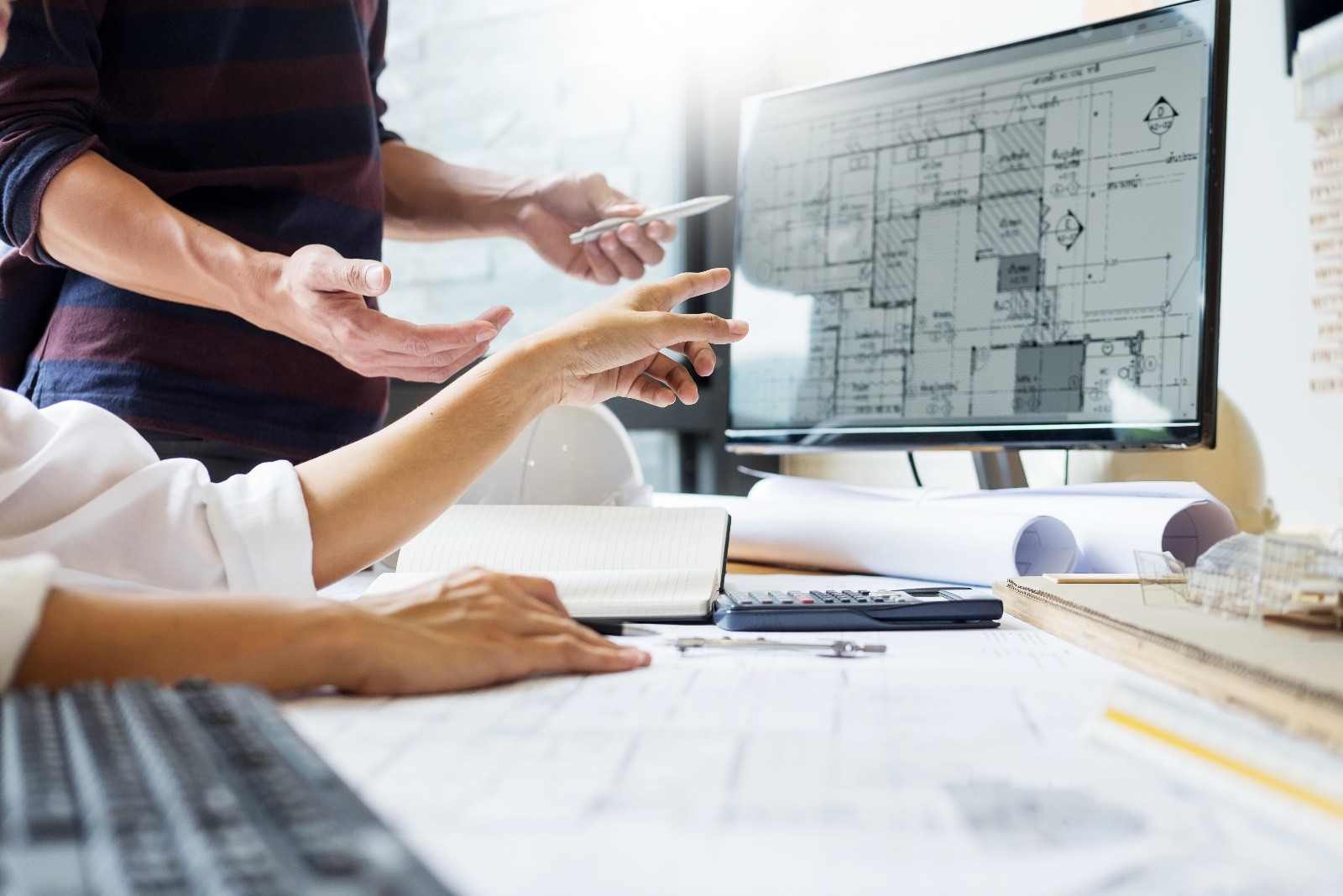 Woman pointing to blueprints on computer