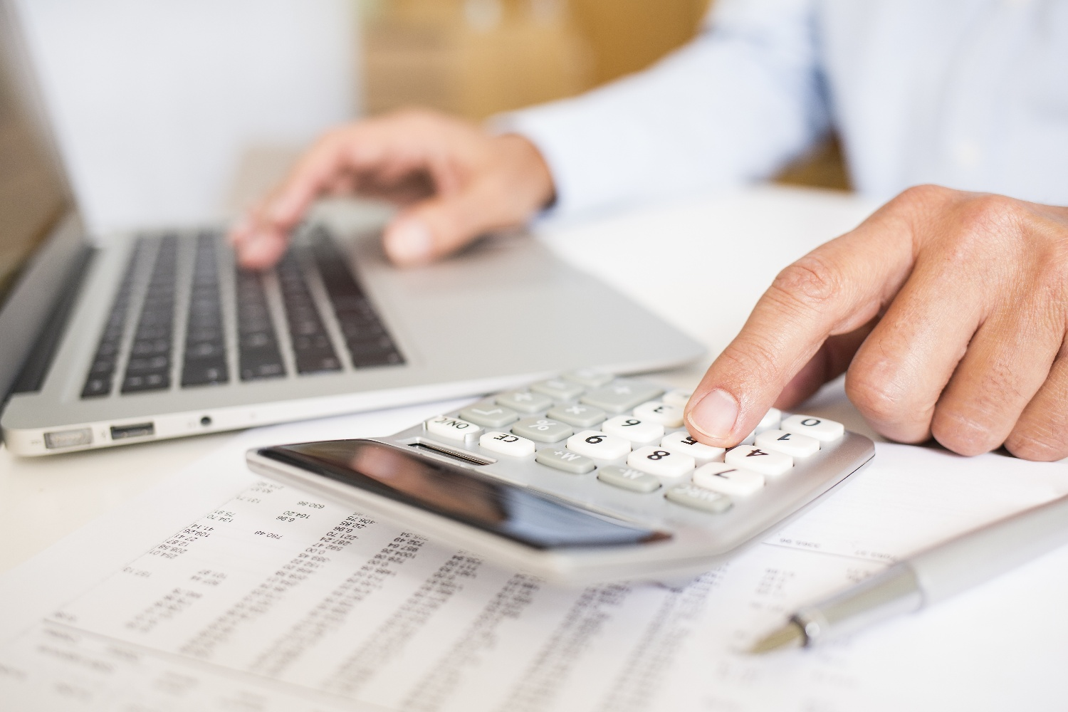 Man working with calculator and laptop